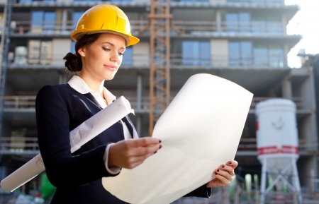 Construction specialist looking at blueprints at construction site photo