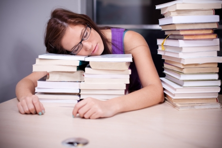 Beautiful young woman falling asleep on stacks of books in the library photo