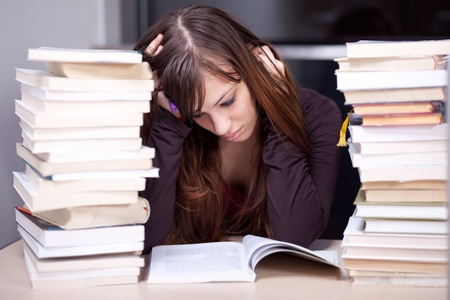 frustrated student: Student buried in books. Studying in the library. Selective focus. Stock Photo