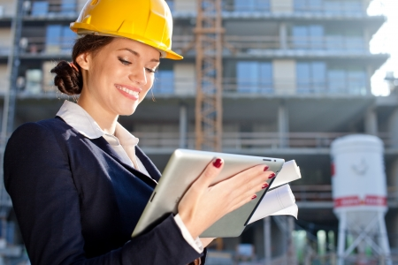 Attractive female construction specialist with a tablet computer at construction site photo