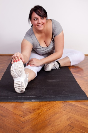Size plus woman stretching on the floor photo