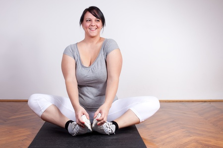 Happy overweight woman exercisingstretching photo