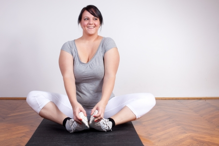 Cheerful overweight woman exercisingstretching photo