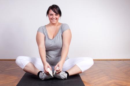 sobre peso: Feliz mujer con sobrepeso el ejercicio  estiramiento Foto de archivo
