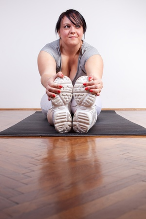 obese woman: Overweight woman exercisingstretching at home