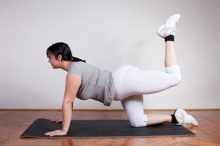 Plus size woman exercising at home photo