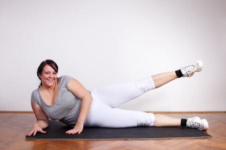 Smiling overweight woman exercising Stock Photo