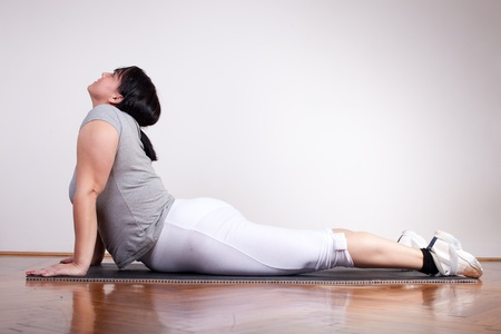 Plus size woman exercisingstretching photo