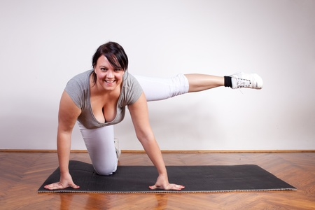 chubby girl: Cheerful overweight woman exercising Stock Photo