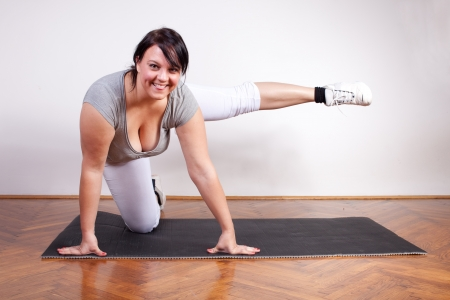 Playful overweight woman exercising on the floor photo