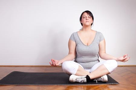 plus sized: Plus sized woman practising yoga