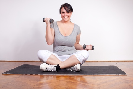 Happy overweight woman lifting weights photo