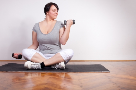 Overweight woman exercising, lifting weights at home photo