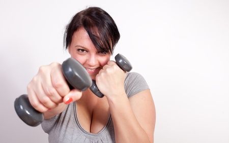 overweight people: Playful overweight woman exercising, lifting weights Stock Photo