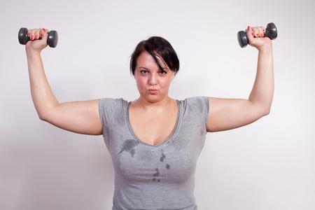 sobre peso: Tamaño de la mujer, más sudor durante el entrenamiento con pesas Foto de archivo