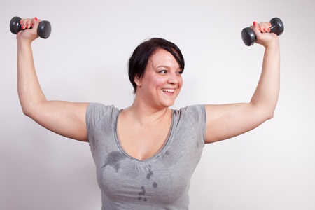 Cheerful overweight woman lifting weights photo