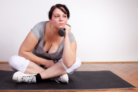 Overweight woman is fed up and tired of exercising photo