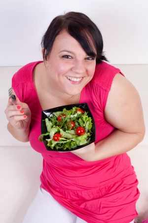 obese woman: Happy overweight woman eating a salad. Selective focus. Stock Photo