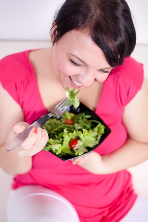 Cheerful overweight woman eating a salad. Selective focus. photo