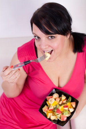 chubby: Overweight woman eating a fruit salad. Selective focus.