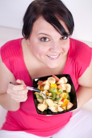 chubby girl: Overweight woman eating a fruit salad. Selective focus.