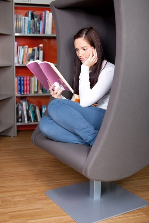 Young woman enjoying a good book in the library photo