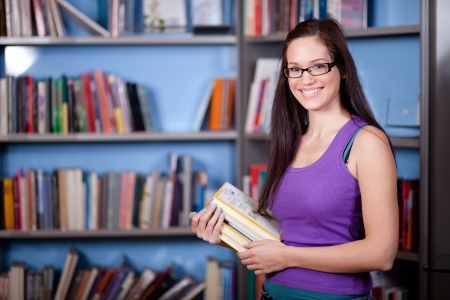 Beautiful young woman standing in front of bookshelves in a librarybookstore photo
