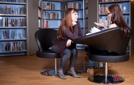 debate: Young women chatting in library