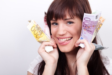 Joyful young woman with her hands full of Euros photo