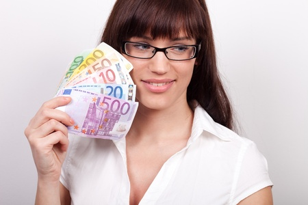 Young woman daydreaming with money in her hands Stock Photo - 12163958