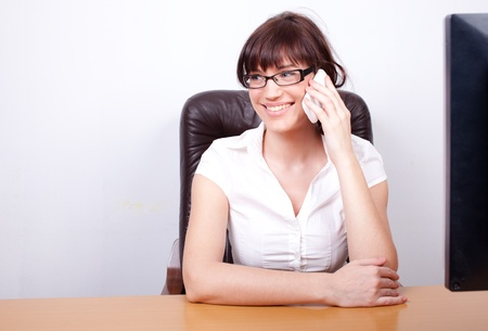 Happy young businesswoman talking on the phone in her office Stock Photo - 12163917