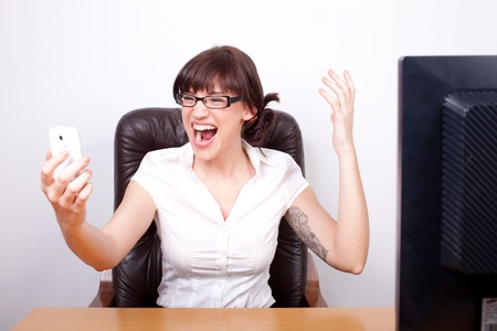 Young businesswoman screaming in rage after receiving bad news over the phone photo