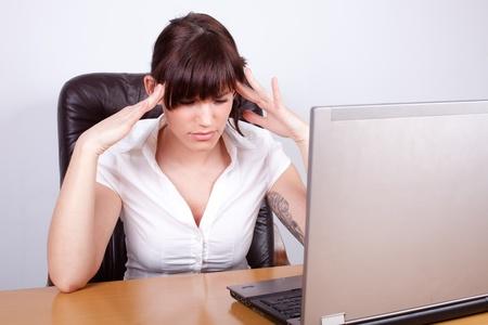 splitting headache: Stressed businesswoman with a splitting headache Stock Photo