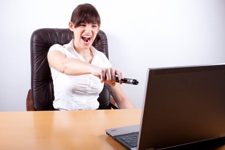 Fuus businesswoman about to shoot a hole through laptop Stock Photo - 12163923