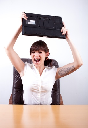 destroying: Angry businesswoman about to throw her laptop. Office rage series. Stock Photo
