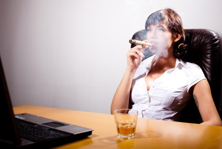 liquor girl: Young businesswoman chillingg in her office, smoking a cigar and drinking whiskey Stock Photo