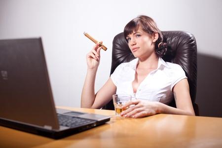 persona fumando: Joven empresaria fumando un puro y bebiendo whisky Foto de archivo