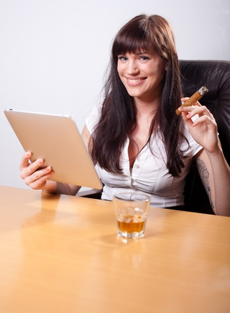 liquor girl: Young businesswoman relaxing in her office, using tablet computer, smoking a cigar and drinking whiskey