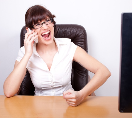 Angry young businesswoman receiving bad news over the phone. Office rage series.  photo