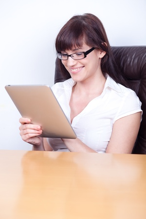 Happy young businesswoman using tablet computer in her office photo