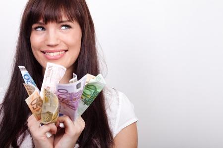 dinero euros: Mujer joven feliz con las manos llenas de billetes de euro