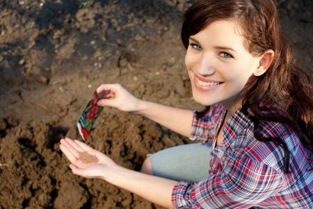 siembra: Joven y bella mujer con las semillas en la mano Foto de archivo