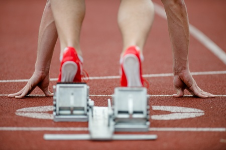 tenseness: Detailed view of a sprinter wearing sprinting shoes with spikes, leaving starting blocks Stock Photo