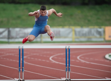 Professional sprinter jumping over a hurdle photo