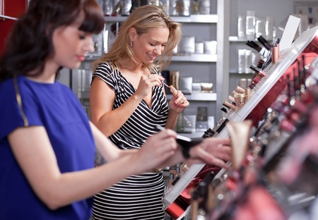 Young women testing and buying powder in a beauty store Stock Photo - 12985877