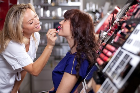 beauty make up: Make up artist applying lipstick to a customer in a beauty store  Selective focus