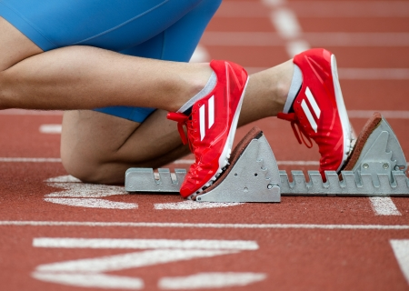 pista de atletismo: Vista detallada de un velocista en la parrilla de salida