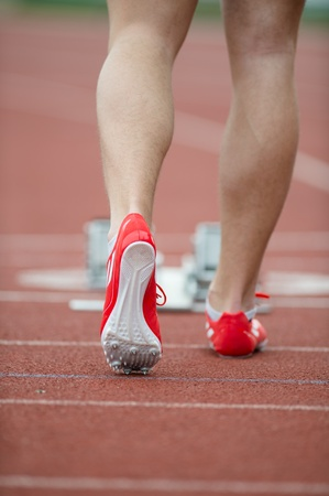 Professional sprinter walking towards the starting line and starting blocks on a running track photo