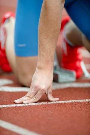tenseness: Close up view of a sprinter in the starting blocks