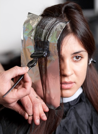 Close up of a hairdresser coloring woman's hair. Selective focus. photo